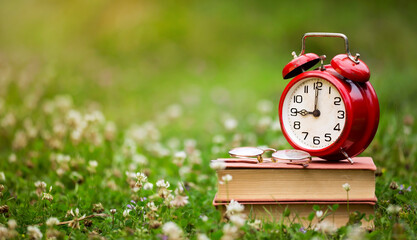 Back to school, homeschooling concept, old retro watch alarm clock on books in the grass. Background with copy space.