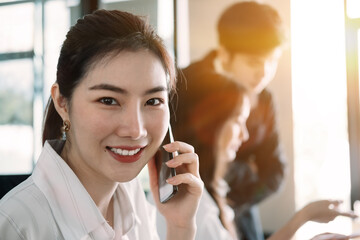 Young asian businesswoman beautiful charming smiling and talking on the mobile phone in meeting room