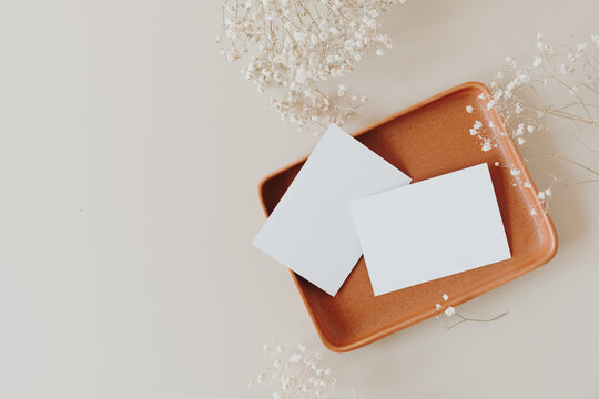 Blank paper cards with mockup copy space on plate and gypsophila flowers on beige background. Minimal business brand template. Flat lay, top view.