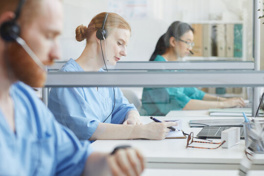 Group of people sitting at the table and talking to clients in medical call center