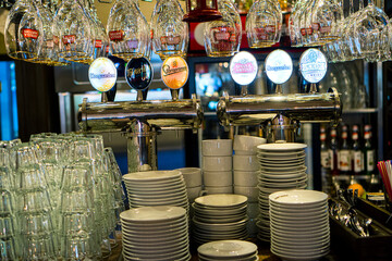 Bar counter in the restaurant with beer faucets, stack of clean plates and drinking glasses. Kharkiv, Ukraine- 28 July, 2020.