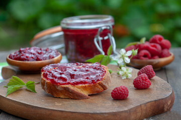 Raspberry jam with fresh raspberries and bread slices on a wooden table. Homemade marmalade, perfect for light, sweet breakfast.