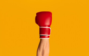 Sportsman wearing boxing glove over orange background, closeup of hand
