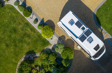 Modern Camper Van with Solar Panels Installed Staying on Residential Driveway Aerial View