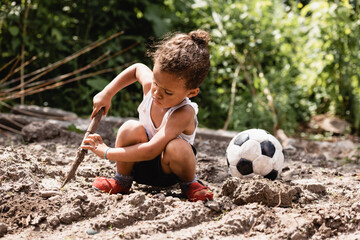 Poor african american child holding wooden twig near soccer ball on dirty road on urban street