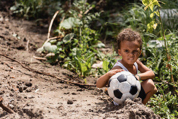 Poor african american boy holding football while sitting near plants on dirty road