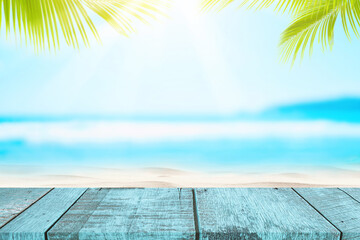 Wall Mural - Blur tropical beach with bokeh sun light wave and palm tree on empty old wood table abstract background.