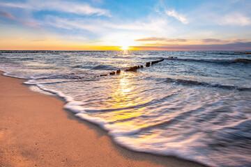 Fototapeta Zachód słońca nad morzem na plaży obraz