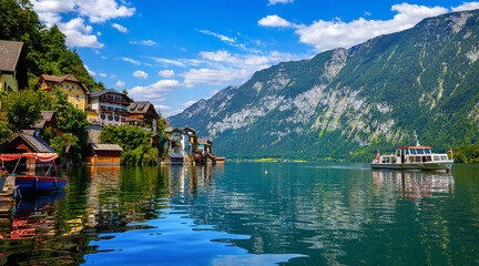 Hallstatt, Austria. Lakeside town in the Austrian Alps. Classic postcard view of famous landscape with passenger ship on a water. Beautiful sunny day with blue sky and clouds. Salzkammergut region