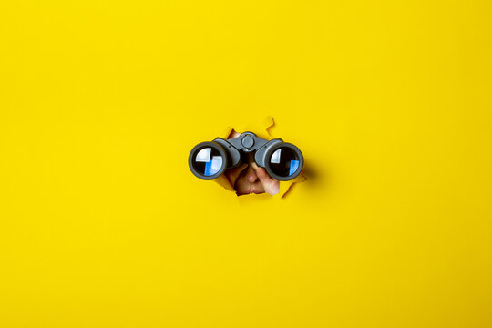 Female hand holds black binoculars on a yellow background. Journey, find and search concept