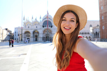 Venice tourist girl on summer vacation taking selfie photo with famous Venice Cathedral in St Mark's Square. European tourism attraction in Italy.