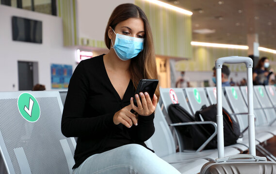 COVID-19 Young tourist woman with surgical mask using phone and sitting respecting social distancing at the airport