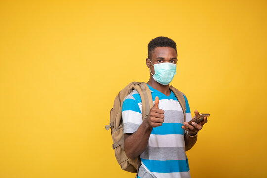 a young black man carrying a backpack and wearing a face mask using his mobile phone, gives a thumbs up