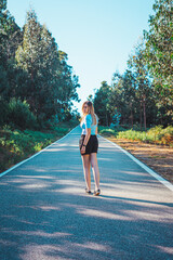 Young caucasian woman walking by an empty road near a forest