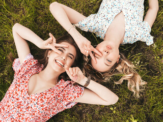 Two young beautiful smiling hipster girls in trendy summer sundress.Sexy carefree women lying on...