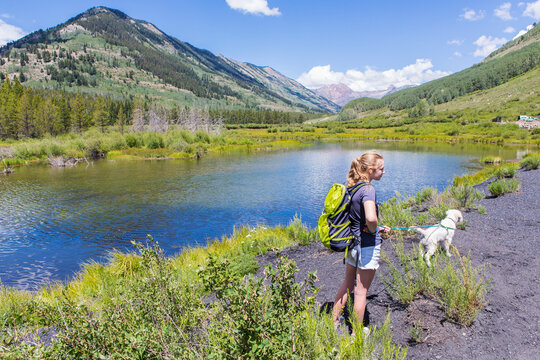 teenage girl hiker with her English Cream Golden Retriever puppy looking at the Slate River, Crested Butte, CO.
