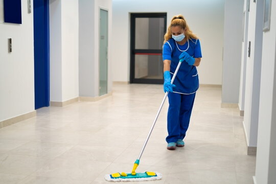 A cleaning lady with the mask on her face mops the floor in an office building
