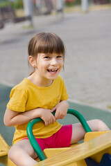 cute girl laughs and rolls on a swing in a kindergarten