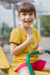 Poster de jardin Doux monstres Happy girl on a seesaw on a playground