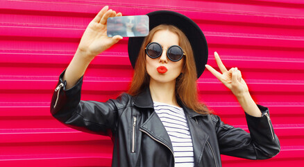 Attractive young woman taking selfie picture by phone blowing red lips sending sweet air kiss over colorful pink background