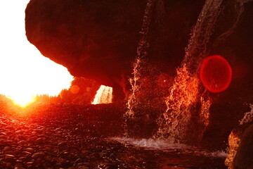 Photo sur Aluminium Rouge mauve red flare over sandcut waterfall at sunset