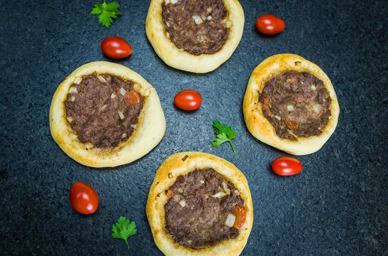 Delicious Lebanese food, legitimate sfihas on a black granite background with tomatoes, lemons.