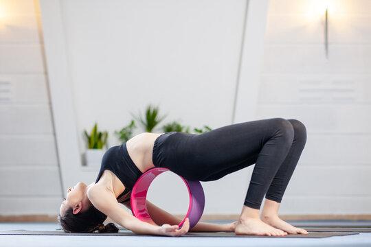 Yoga girl exercising on yoga wheel in a studio.