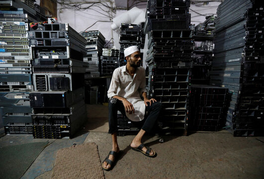 Man sits in front of e-waste from computers at a workshop in New Delhi