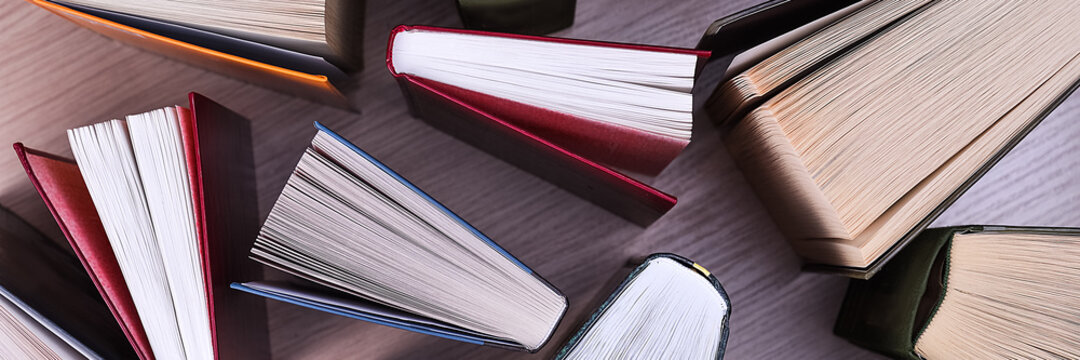 Books top view. They stand ajar on the table, the sheets spread out like a fan. Back to school. Education. Reading.