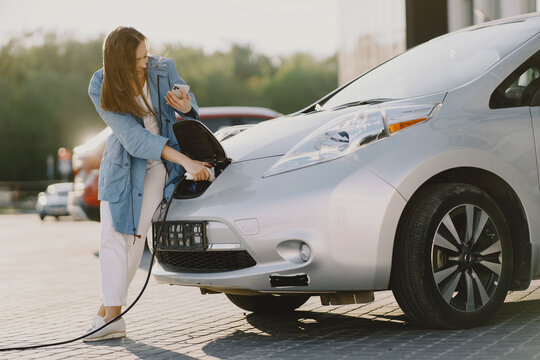 Charging electro car at the electric gas station. Woman standing by the car.