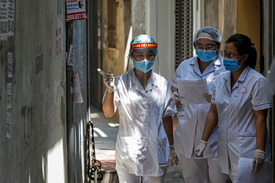 Healthcare workers are seen at a lane near the house of a coronavirus disease (COVID-19) patient as they investigate infection links in Hanoi