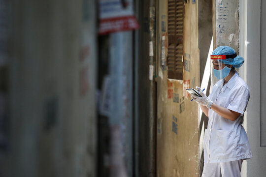 A healthcare worker is seen at a lane near the house of a coronavirus disease (COVID-19) patient while investigating infection links in Hanoi