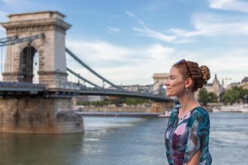 Young woman daydreaming at Szechenyi Chain Bridge at Budapest