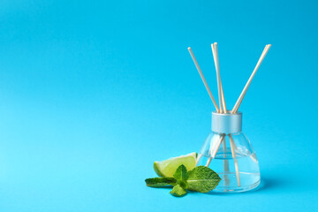 Reed diffuser with lime and mint on color background