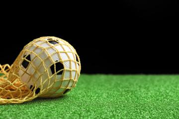 Soccer ball on green field against dark background