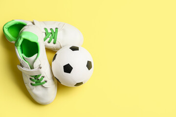 Soccer ball and shoes on color background