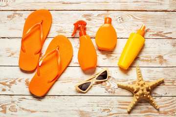 Beach accessories with sunscreen cream on white wooden background