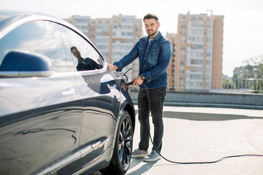Full length portrait of young handsome bearded man in casual wear, standing at the charging station and holding a plug of the charger for an electric car. Eco electric car concept