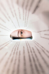 Eye of the student between the book pages. Concept of education and self-learning
