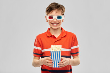 cinema and people concept - portrait of happy smiling boy in 3d movie glasses eating popcorn from...