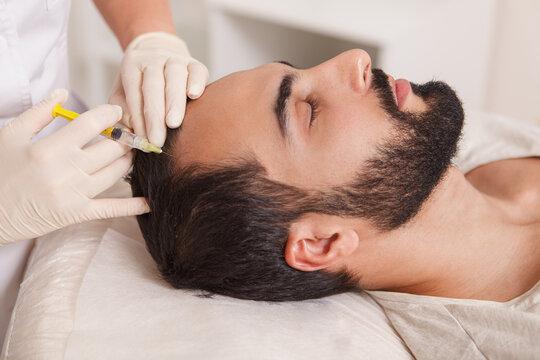 Bearded man getting anti hair loss treatment by beautician