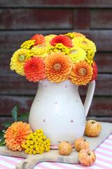 Dahlienstrauß in Gelb und Orange in rustikaler Blumenvase