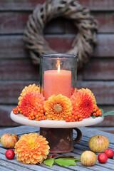 Sommerdekoration in Orange mit Kerze, Dahlien und Ebereschenbeeren