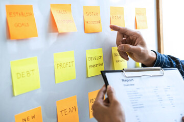 Two creative meeting and planning use post it notes on board to share idea