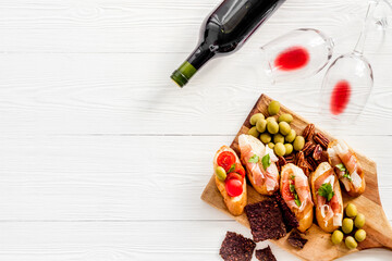 Fototapete - Bruschetta with prosciutto and red wine in glasses from above copy space