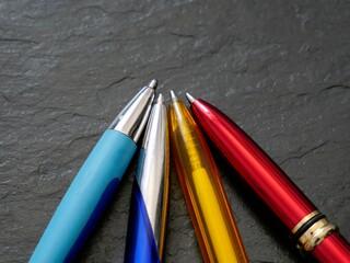 Vier bunte Kugelschreiber, dunkler Hintergrund