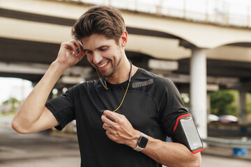 Image of athletic smiling sportsman using earphones while working out