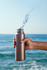 Tuinposter Europa pouring water out of an aluminum reusable bottle