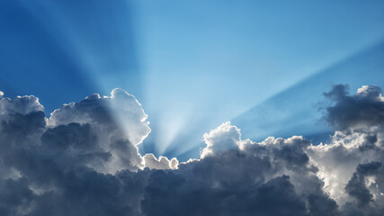 Sun rays behind dark clouds in a blue sky, horizontally panoramic Fototapete