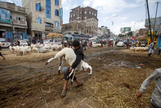 A man carries a sheep at a livestock market ahead of the Eid al-Adha festival amid the coronavirus disease (COVID-19) pandemic in Sanaa